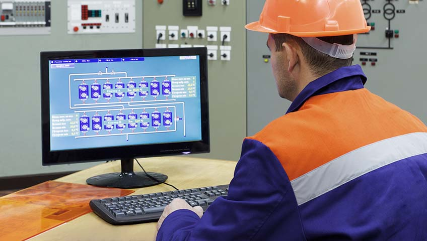 Engineer at the computer on main control panel of gas compressor station, focus on back